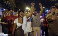 Government supporters chant slogans praising Venezuela's late President Hugo Chavez at opposition supporters, outside a a polling station that had remained open about 20 minutes past the allotted time, in Caracas, Venezuela, Sunday, April 14, 2013. Although no was waiting to vote, the polling station remained open past 6:00 p.m., until demands by a group of opposition supporters were met for the station to be closed. Voters were deciding Sunday whether to elect interim President Nicolas Maduro, who served as late President Hugo Chavez's foreign minister and vice president or opposition candidate Henrique Capriles in a special presidential election to replace Chavez who died of cancer on March 5. (AP Photo/Ariana Cubillos)