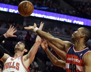 In this April 17, 2013 file photo, Washington Wizards center Jason Collins, right, battles for a rebound against Chicago Bulls guard Kirk Hinrich during the first half of an NBA basketball game in Chicago. Jason Collins has become the first male professional athlete in the major four American sports leagues to come out as gay. Collins wrote a first-person account posted Monday on Sports Illustrated's website. The 34-year-old Collins has played for six NBA teams in 12 seasons. He finished this past season with the Washington Wizards and is now a free agent. He says he wants to continue playing.  (AP Photo/Nam Y. Huh, File)