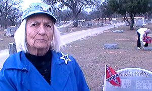 Joyce Whitis explains the purpose of placing Confederate flags on graves at West End Cemetery. daughters of the confederacy. (Houston Hall, Texan News Service)