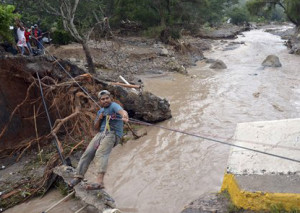 A man uses a makeshift zip line to cross a river after a bridge collapsed under the force of the rains caused by Tropical Storm Manuel near the town of Petaquillas, Mexico, Wednesday, Sept. 18, 2013. The death toll from devastating twin storms climbed to 80 on Wednesday as isolated areas reported to the outside world. Mexican officials said that a massive landslide in the mountains north of Acapulco could drive the number of confirmed dead even higher.  Photo courtesy of the Associated Press