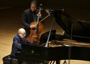 Holocaust survivor George Horner, front left, performs with cellist Yo-Yo Ma, top, on stage at Symphony Hall Tuesday, Oct. 22, 2013, in Boston. The 90-year-old pianist made his orchestral debut with Ma, where they played music composed 70 years ago at the Nazi concentration camp where Horner was imprisoned.  (AP Photo/Steven Senne)