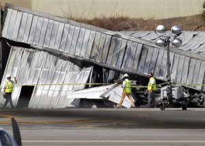 National Transportation Safety Board (NTSB) investigators walk by the tail of the private jet, which crashed into a hangar at the Santa Monica Municipal Airport in California, as they await the arrival of a crane to access the plane. As a result of the Oct. 1 federal government partial shutdown almost all of the board's 400 employees were furloughed, an NTSB spokeswoman said. Across America the government's work is piling up, and it's not just paperwork.  (AP Photo/Nick Ut)