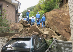 Fire fighters stand on rocks fallen from a cliff over a garage and a road in a residential area in Kamakura, southwest of Tokyo, after a powerful typhoon hit Japan's metropolitan area Wednesday morning, Oct. 16, 2013. Typhoon Wipha triggered landslides and caused multiple deaths on a Japanese island off Tokyo, before sweeping up the country's east coast, grounding hundreds of flights and paralyzing public transportation in Tokyo during Wednesday morning's rush hour.  (AP Photo/Kyodo News)