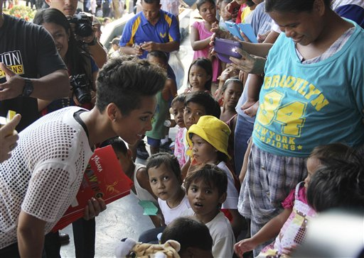 In this photo released by the Philippine Air Force, Grammy-winning singer Alicia Keys, left, smiles at a typhoon survivor as she visits the Villamor Air Base in suburban Pasay, south of Manila, Philippines, Monday Nov. 25, 2013. Keys visited the air force base to bring cheer to hundreds of evacuees from eastern Philippine provinces wracked by Typhoon Haiyan earlier this month.  (AP Photo/Philippine Air Force)