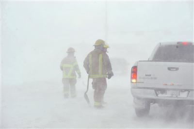 Amarillo emergency personnel assisted a stranded motorist on the I-40 service road Monday, Feb. 25, 2013 in Amarillo, Texas. A blizzard packing 50 mph wind gusts and more than 11 inches of snow blasted Amarillo and Texas Panhandle Monday, making travel nearly impossible. Interstate 40 and many major highways in the Panhandle have been closed.  (AP Photo/The Amarillo Globe News,Michael Schumacher)