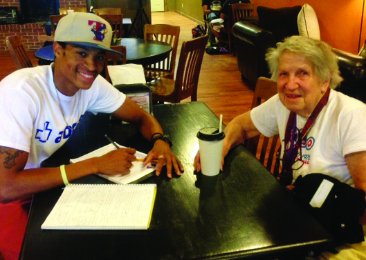 Texan News Service writer Dawelo Sears sits with 90-year-old student Dorris Kent at Beans and Franks during an interview about life as a college student.  (Texan News Service)