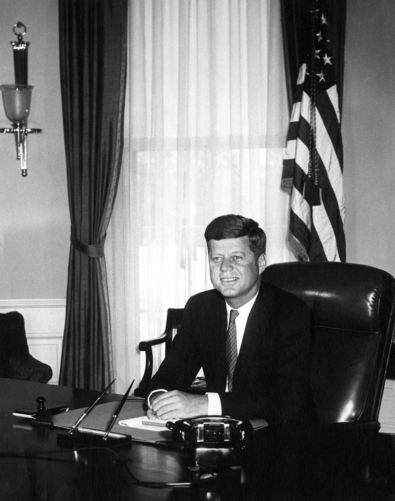 Portrait photo of President John F. Kennedy at his desk in the Oval Office. This is the first White House photograph made of the President at his desk.  (Abbie Rowe, White House Photographs, John F. Kennedy Presidential Library and Museum, Boston)