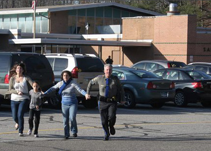 In this Friday, Dec. 14, 2012, file photo provided by the Newtown Bee, a police officer leads two women and a child from Sandy Hook Elementary School in Newtown, Conn., where a gunman opened fire, killing 26 people, including 20 children. A prosecutor is planning to release a report on the investigation into the massacre at Sandy Hook Elementary School on Monday, Nov. 25, 2013, but the public will have to wait longer for the Connecticut state policeís full accounting of the crime.  (AP Photo/Newtown Bee, Shannon Hicks, File) MANDATORY CREDIT: NEWTOWN BEE, SHANNON HICKS