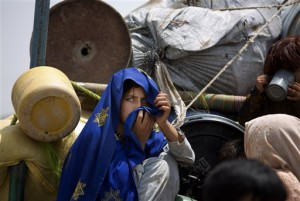 A Pakistani tribal girl sits next to her belongings on a truck after arriving to Bannu, Pakistan, Wednesday, June 18, 2014. Thousands of villagers fled as Pakistani army relax a curfew in troubled North Waziristan. Pakistani jets pounded targets in the country's northwest in major offensives  designed to root out safe havens in the volatile region. (AP Photo/B.K. Bangash)