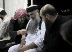 In this Wednesday, Sept. 24, 2014 photo, radical al-Qaida-linked preacher Abu Qatada, center, listens to the renowned jihadi ideologue, Abu Mohammed al-Maqdisi, second left, on the day Abu Qatada was released from Jordanian prison after an acquittal on security charges, in Amman, Jordan. Abu Qatada and al-Maqdisi, held court on the rooftop of a villa whispering to each other and rising occasionally from plastic chairs to greet supporters. The two have denounced some of the Islamic State group's practices as un-Islamic - comments some analysts say have turned the preachers into assets in Jordan's campaign to contain the Islamic State, which is believed to have attracted thousands of followers in Jordan. (AP photo/Mohammad Hannon)