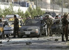 NATO and Afghan security forces inspect the site of a suicide attack in Kabul, Afghanistan, Tuesday, Sept. 16, 2014. A Taliban suicide car bomber attacked a foreign motorcade just a couple hundred yards (meters) from the U.S. Embassy, unleashing a blast that injured at least 13 people and rattled nearby neighborhoods, police officials said. (AP Photo/Rahmat Gul)