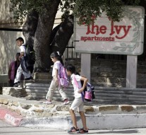 Children arriving home from school walk past the main entrance to The Ivy Apartments complex, Wednesday, Oct. 1, 2014, in Dallas. The man diagnosed with having the Ebola virus was staying at the complex with family. (AP Photo/Tony Gutierrez)