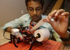 Shubham Banerjee works on his lego robotics braille printer at home Tuesday, Jan. 6, 2015, in Santa Clara, Calif. Banerjee launched a company to develop a low-cost machine to print Braille materials for the blind. It's based on a prototype he built with his Lego robotics kit for a school science fair project. Last month, tech giant Intel Corp. invested in his startup, Braigo Labs, making the 8th grader the youngest entrepreneur to receive venture capital funding. (AP Photo/Marcio Jose Sanchez)