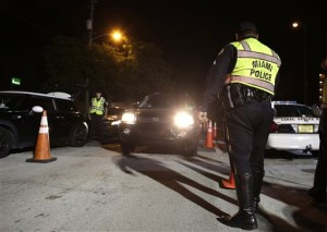 In this Thursday, Jan. 29, 2015 photo, a Miami police officer guides vehicles through a drunk-driving checkpoint in Miami. A South Florida DUI attorney contends the commonly-used checkpoints violate driver's constitutional rights. (AP Photo/Lynne Sladky)