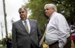 CORRECTS RALLY TO VIGIL - North Charleston Police Chief Eddie Driggers, left, and Mayor Keith Summey wait for a vigil to begin at a makeshift memorial where Walter Scott was fatally shot by a white police officer after he fled a traffic stop, Sunday, April 12, 2015, in North Charleston, S.C. The officer, Michael Thomas Slager, has been fired and charged with murder. (AP Photo/David Goldman)