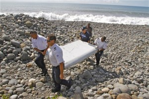In this July 29, 2015, photo, French police officers carry a piece of debris from a plane known as a flaperon in Saint-Andre, Reunion Island. Malaysian Prime Minister Najib Razak announced on Thursday, Aug. 6, 2015, that a wing piece that washed up on Reunion Island last week is from the missing Malaysia Airlines Flight 370. However, French, U.S. and Australian authorities stopped short of full confirmation, frustrating relatives with mixed messages. (AP Photo/Lucas Marie)